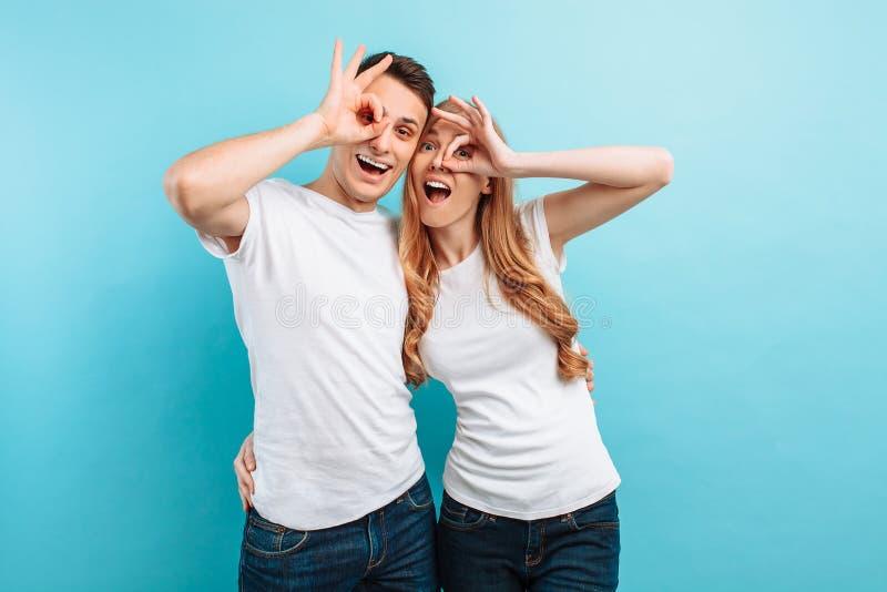 Jong paar in liefde, man en vrouw die, die en een gebaar met twee vingers, op lichtblauwe achtergrond verheugen zich tonen royalty-vrije stock afbeeldingen