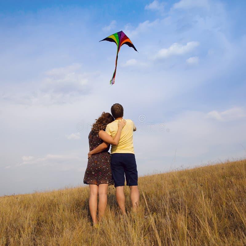 Jong paar in liefde met het vliegen van een vlieger bij platteland stock fotografie