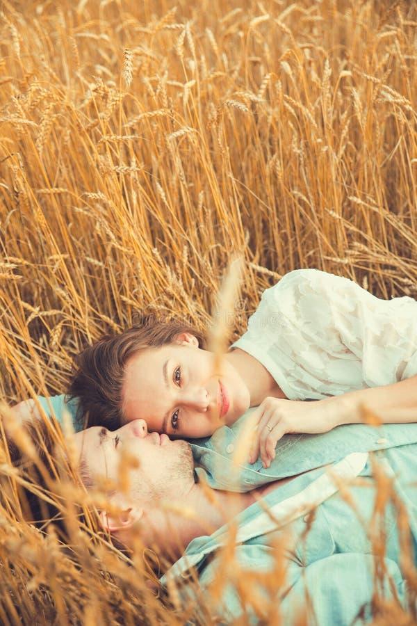 Jong paar in liefde openlucht Het Koesteren van het paar Jong mooi paar in liefde die en op het gebied op zonsondergang blijven k royalty-vrije stock foto's