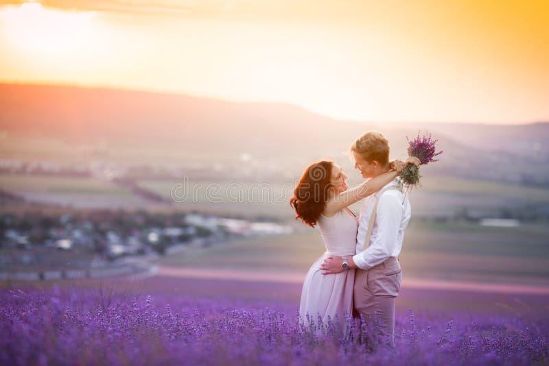 Jong paar in liefdebruid en bruidegom, huwelijksdag in de zomer Geniet van een ogenblik van geluk en liefde op een lavendelgebied royalty-vrije stock afbeeldingen