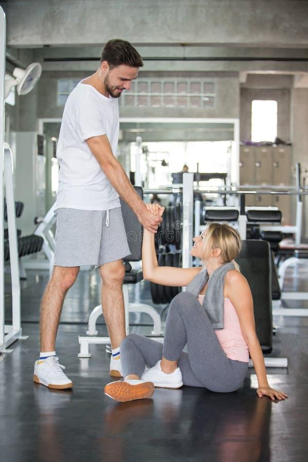 jong paar in liefdeoefening samen in geschiktheidsgymnastiek de vriend die van de sportmens meisje helpen op te staan of van vloe stock fotografie