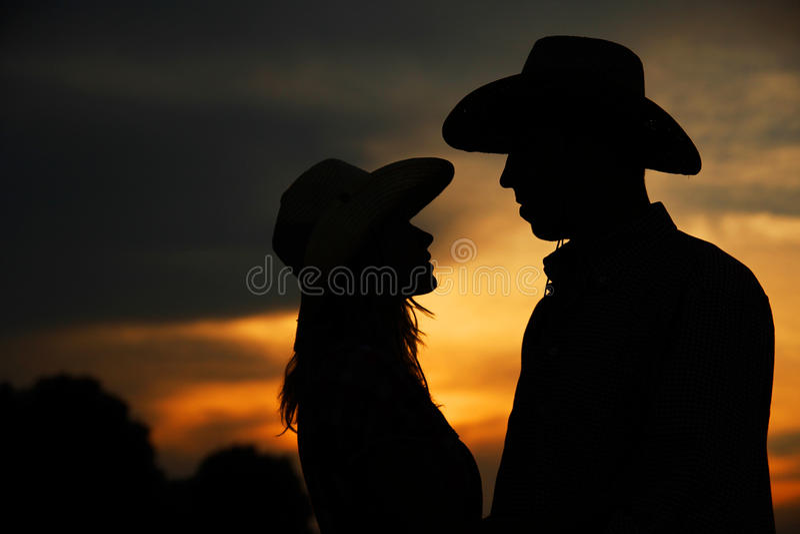 Jong paar in liefdesilhouet in cowboyhoeden royalty-vrije stock afbeeldingen