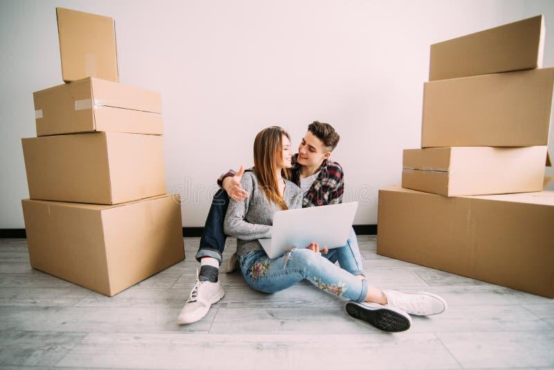 Jong paar in liefdezitting op de vloer van hun nieuwe flat, planningsopknapbeurt en het zoeken naar ideeën op laptop comput royalty-vrije stock fotografie