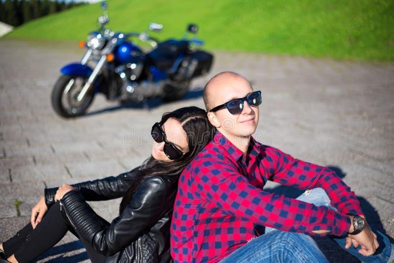 Jong paar in liefdezitting op de weg met retro motor royalty-vrije stock afbeeldingen