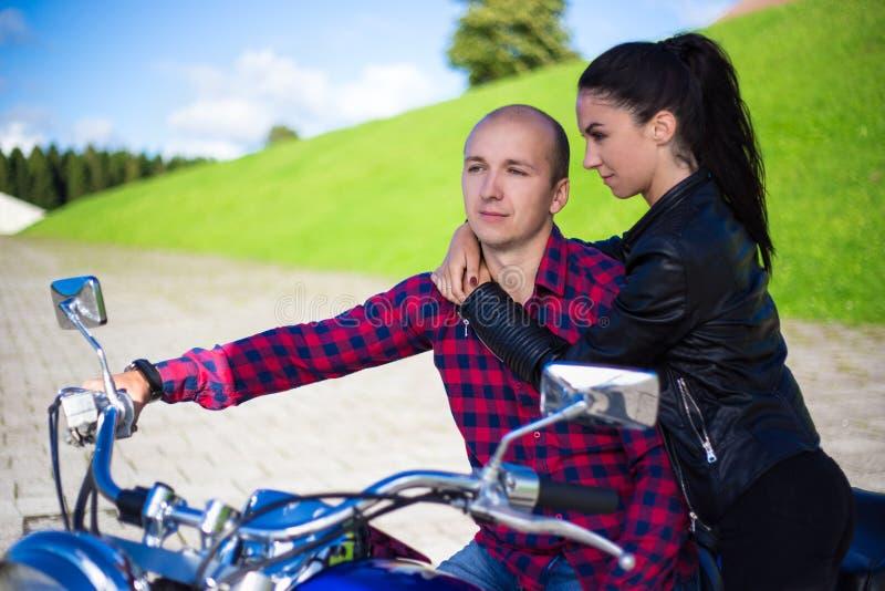 Jong paar in liefdezitting op retro motorfiets royalty-vrije stock afbeeldingen