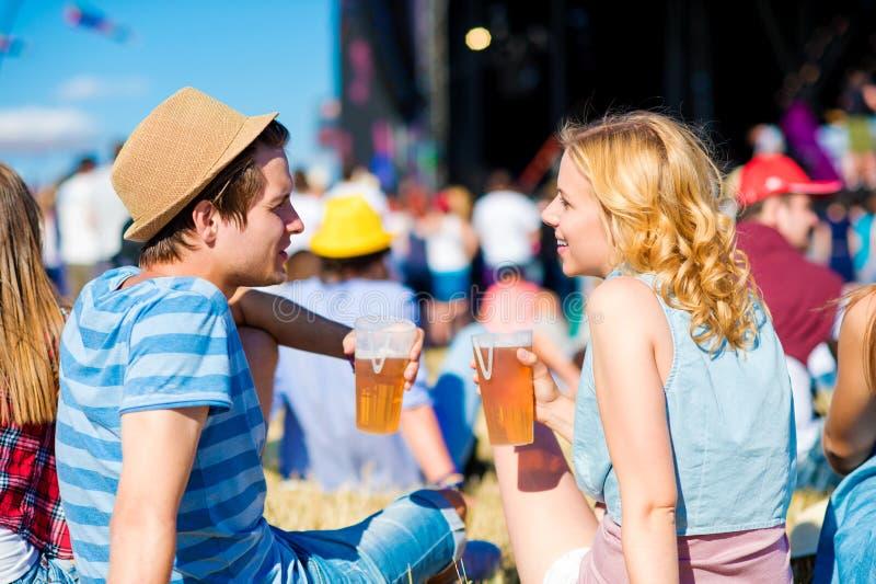 Jong paar met bier bij het festival van de de zomermuziek royalty-vrije stock fotografie