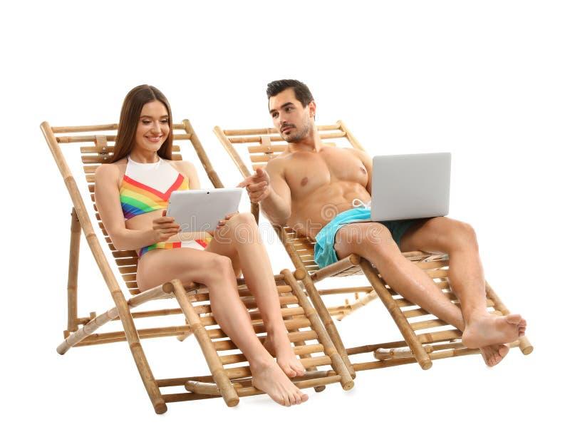 Jong paar met computers op de witte achtergrond van zonlanterfanters De toebehoren van het strand royalty-vrije stock foto