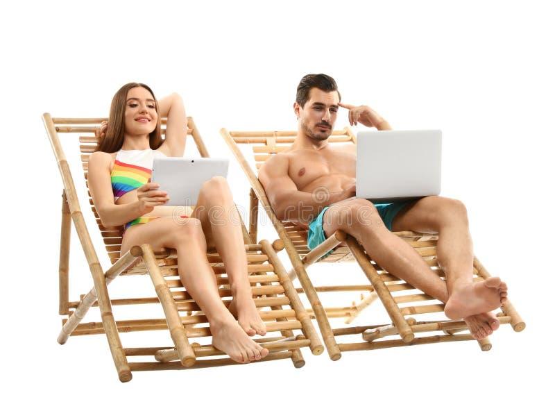 Jong paar met computers op zonlanterfanters tegen witte achtergrond Strand royalty-vrije stock foto's