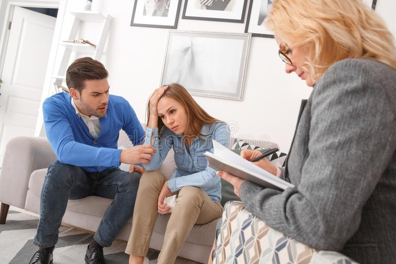 Jong paar met de therapieechtgenoot van de psycholoogfamilie het proberen te spreken stock foto's