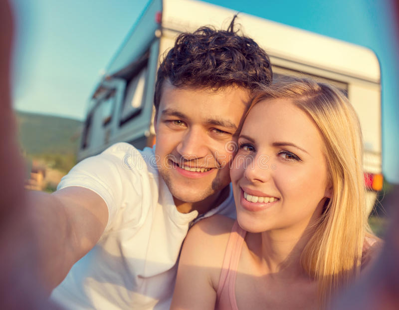 Jong paar met een kampeerautobestelwagen royalty-vrije stock afbeelding