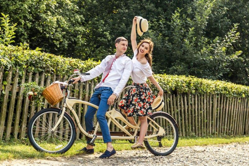 Jong paar met fiets achter elkaar in park De jongeren houdt hoeden in hun handen en glimlach Op de rug van de boomomheining stock afbeeldingen