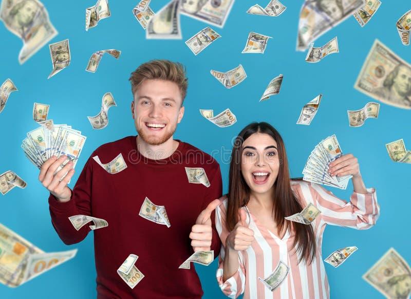 Jong paar met geld op kleur royalty-vrije stock afbeeldingen