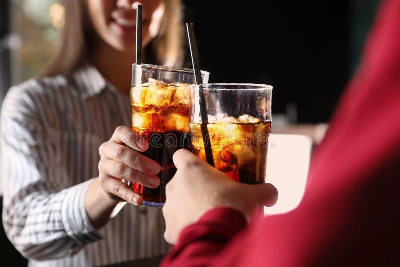 Jong paar met glazen van het verfrissen van kola, close-up royalty-vrije stock afbeeldingen