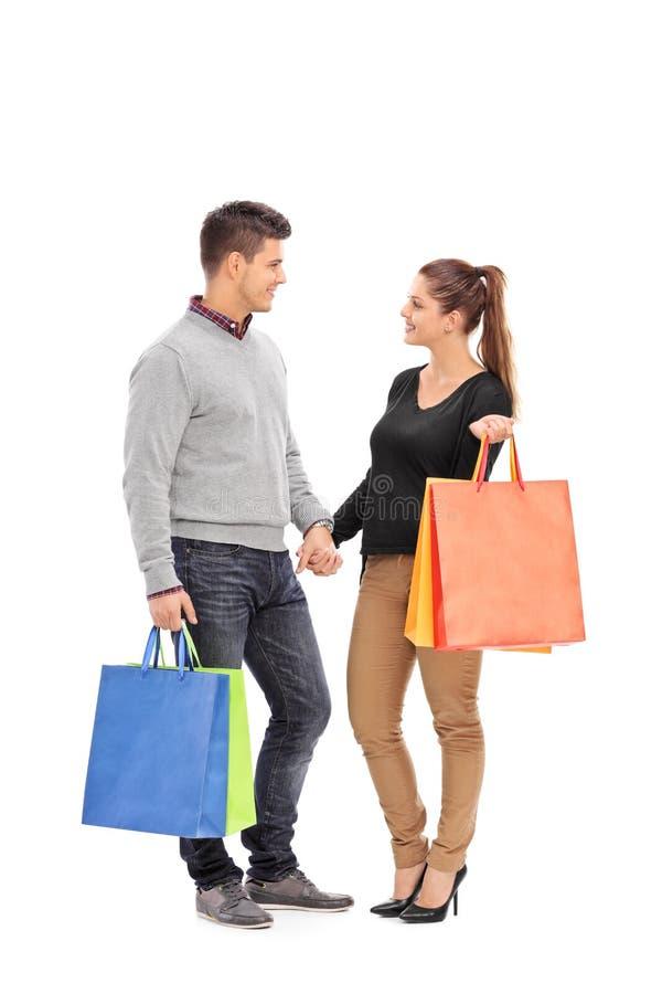 Jong paar met het winkelen zakken stock afbeeldingen