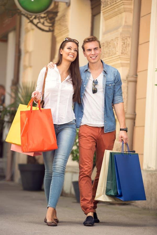 Jong paar met het winkelen zakken stock foto's