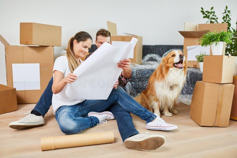 Jong paar met hond en bouwtekening royalty-vrije stock afbeeldingen