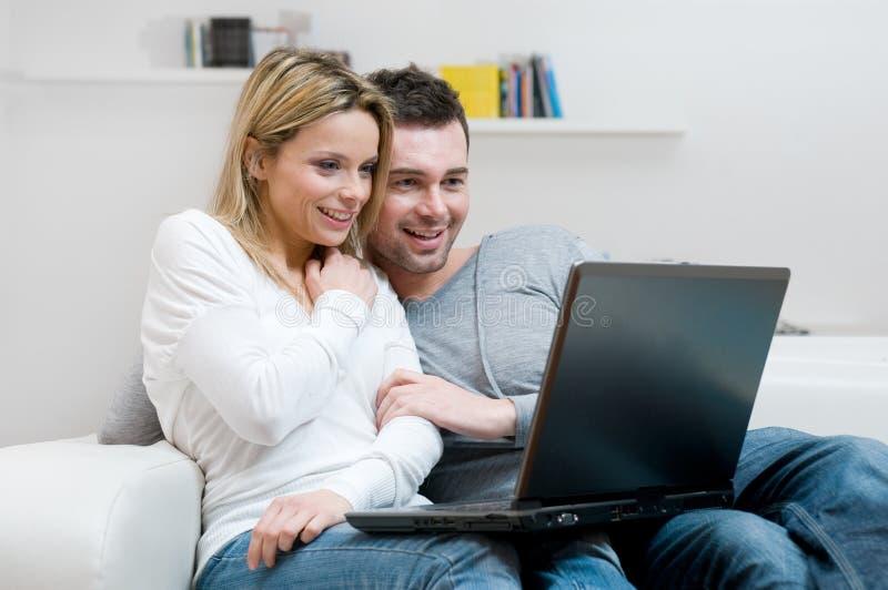 Jong paar met laptop thuis stock foto's