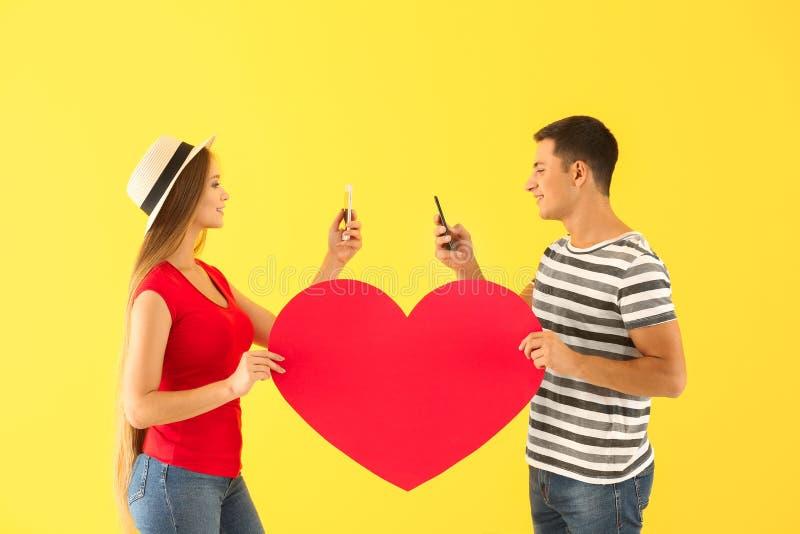 Jong paar met mobiele telefoons en groot document hart op kleurenachtergrond stock afbeeldingen