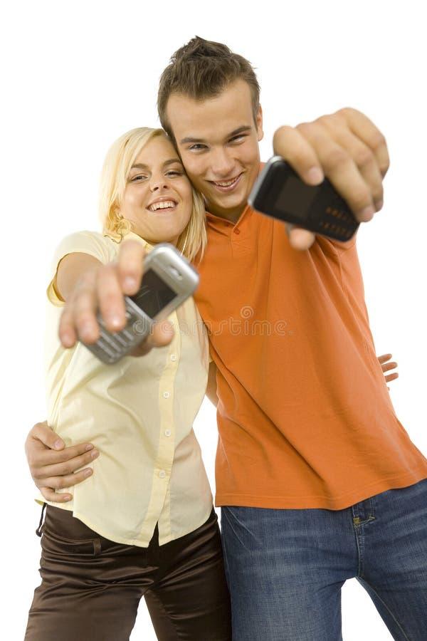 Jong paar met mobiles stock fotografie