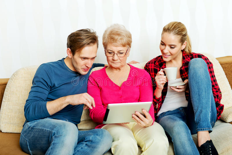 Jong paar met oude vrouwenzitting op laag en het letten van op iets op tablet stock foto