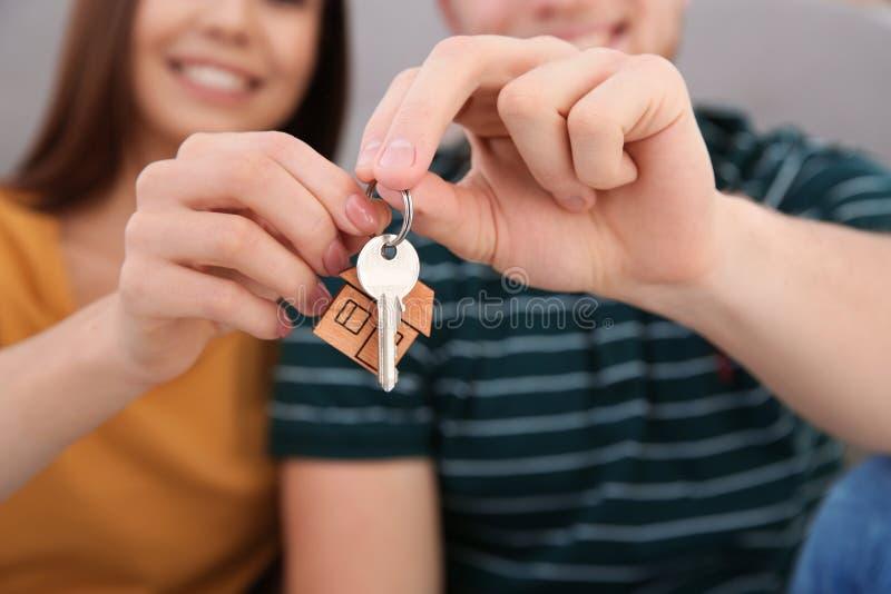 Jong paar met sleutel van hun nieuw huis binnen, close-up royalty-vrije stock afbeelding