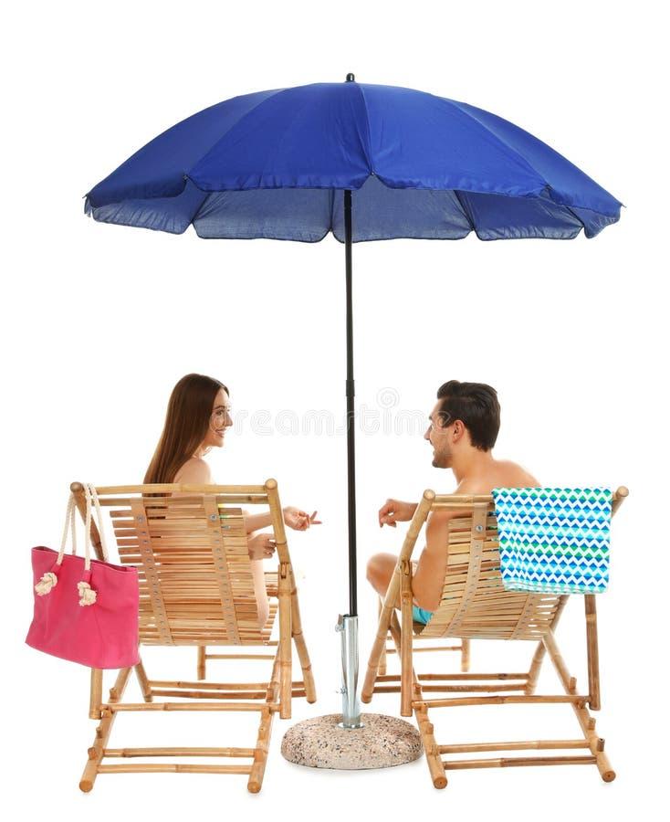 Jong paar met strandtoebehoren op zon tegen witte achtergrond stock foto