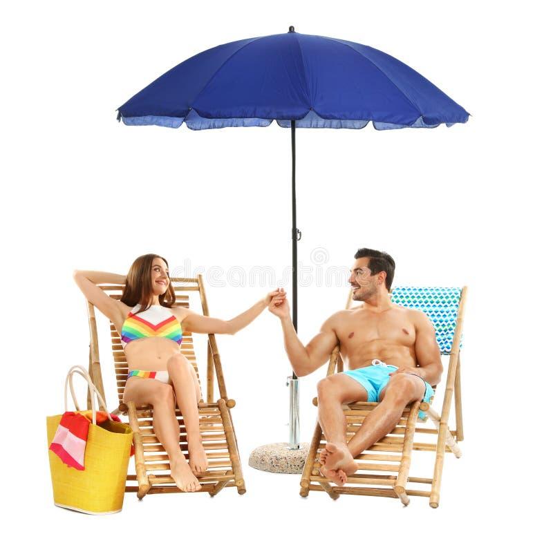 Jong paar met strandtoebehoren op zon tegen witte achtergrond stock fotografie