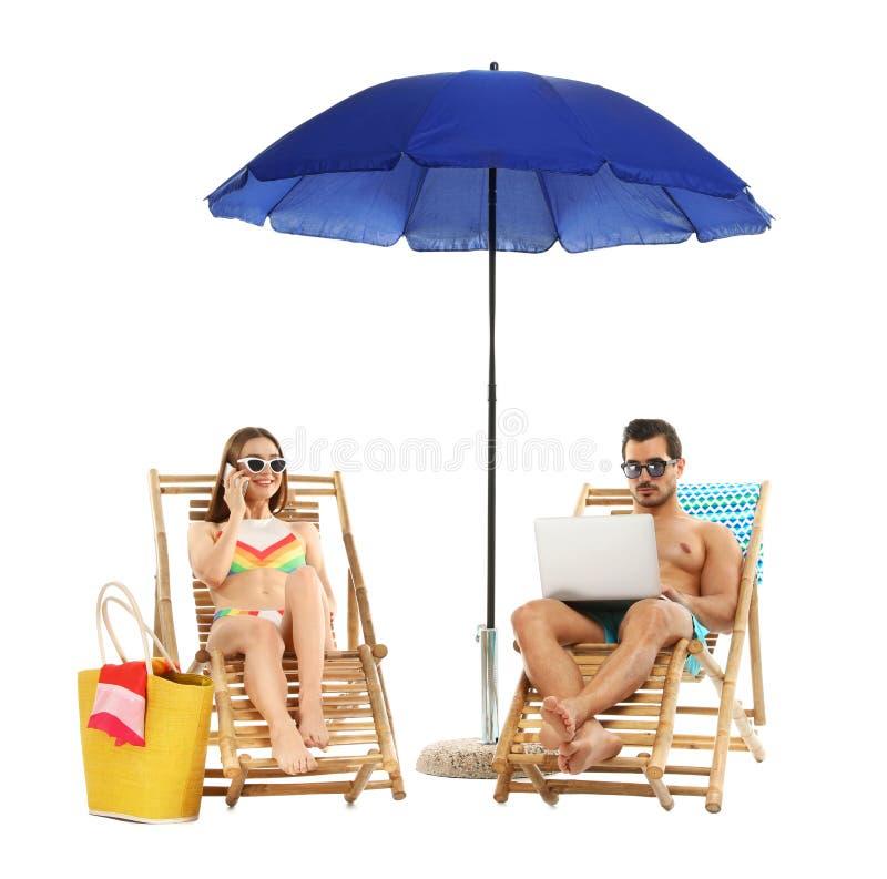 Jong paar met strandtoebehoren op zonlanterfanters tegen wit stock foto