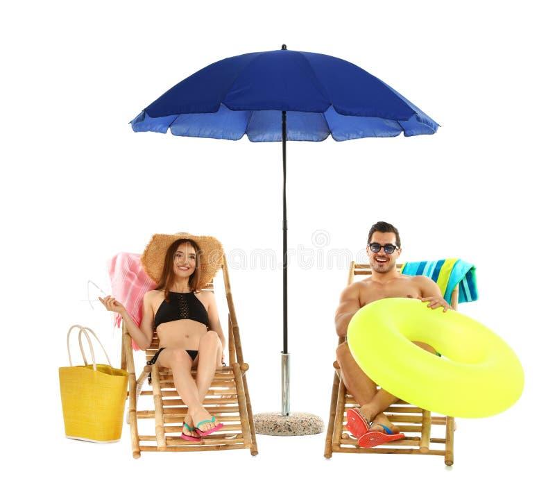 Jong paar met strandtoebehoren op zonlanterfanters tegen wit stock afbeeldingen