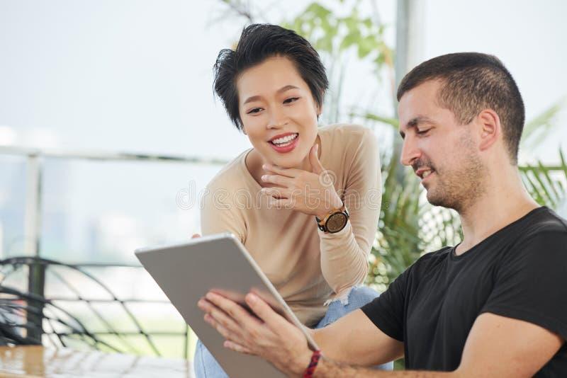 Jong paar met tabletpc in koffie royalty-vrije stock afbeelding