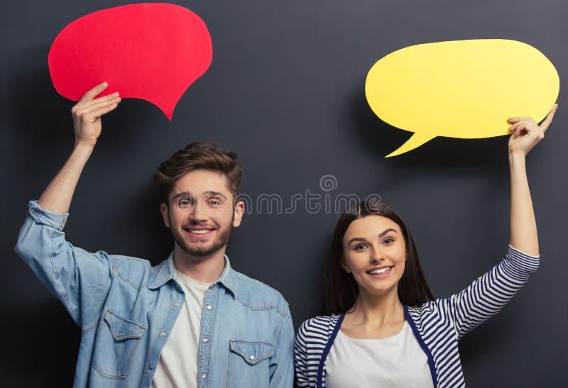 Jong paar met toespraakbellen stock fotografie
