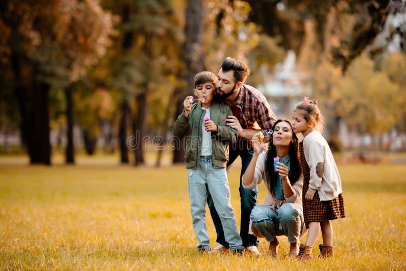 Jong paar met twee kinderen die zeepbels blazen stock afbeeldingen