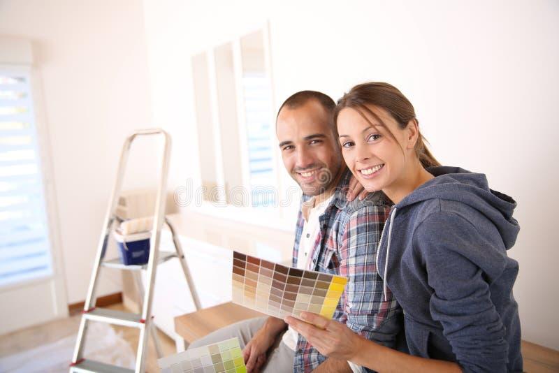 Jong paar in nieuw huis het verfraaien stock afbeelding