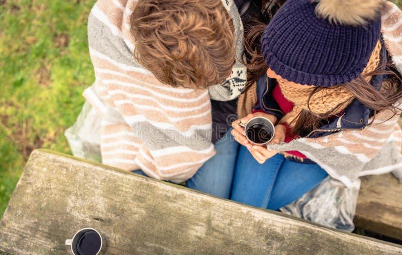 Jong paar onder deken die hete drank in a hebben stock foto