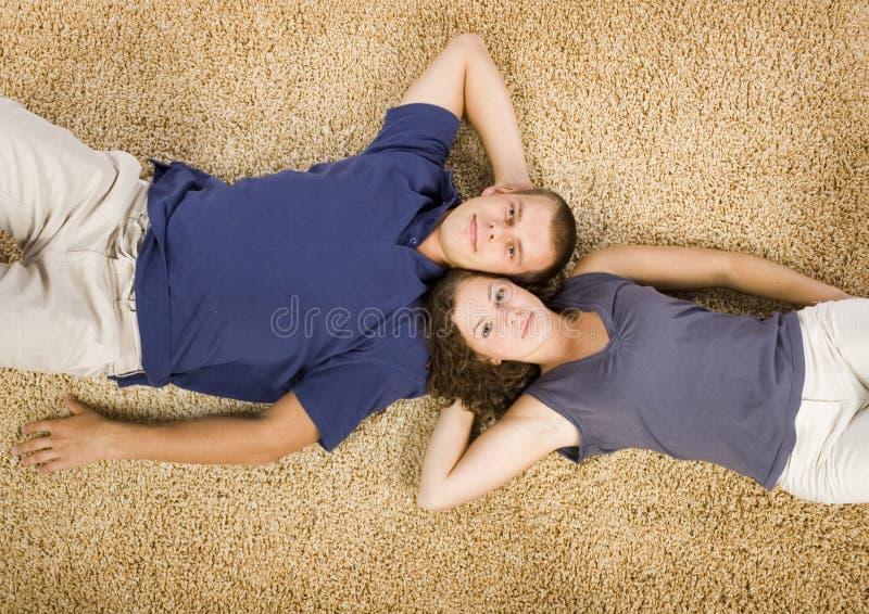 Jong paar op beige tapijt stock afbeeldingen