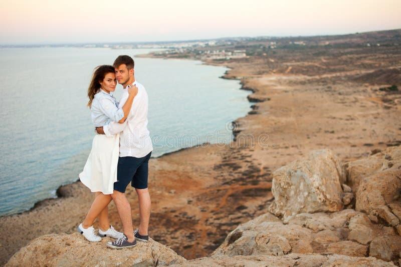 Jong paar op de rots met de spectaculaire mening over de achtergrond stock fotografie