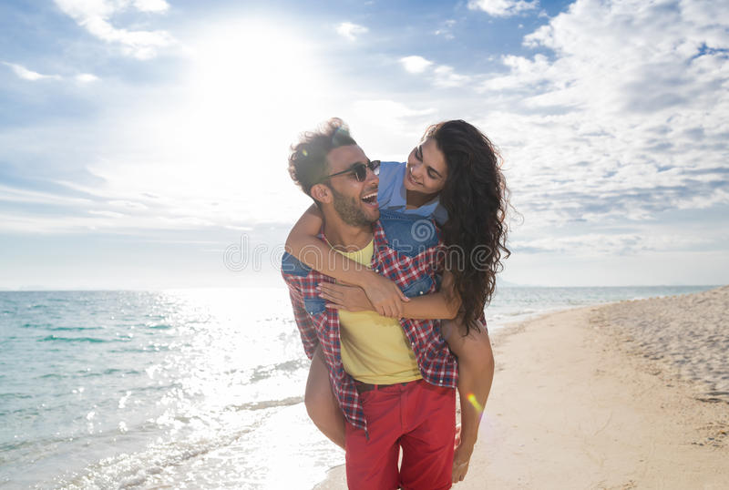 Jong Paar op de Vakantie van de Strandzomer, Gelukkige Glimlachende Mens Carry Woman Back Seaside royalty-vrije stock afbeelding