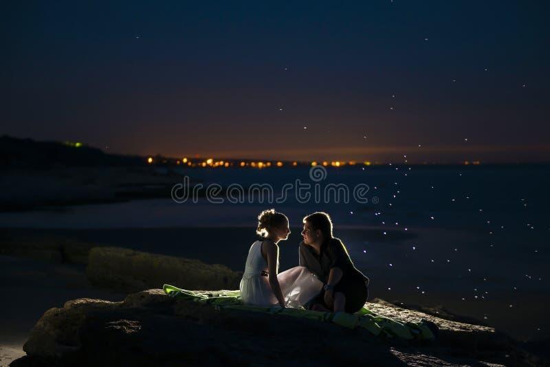Jong paar op een avondkust stock afbeeldingen