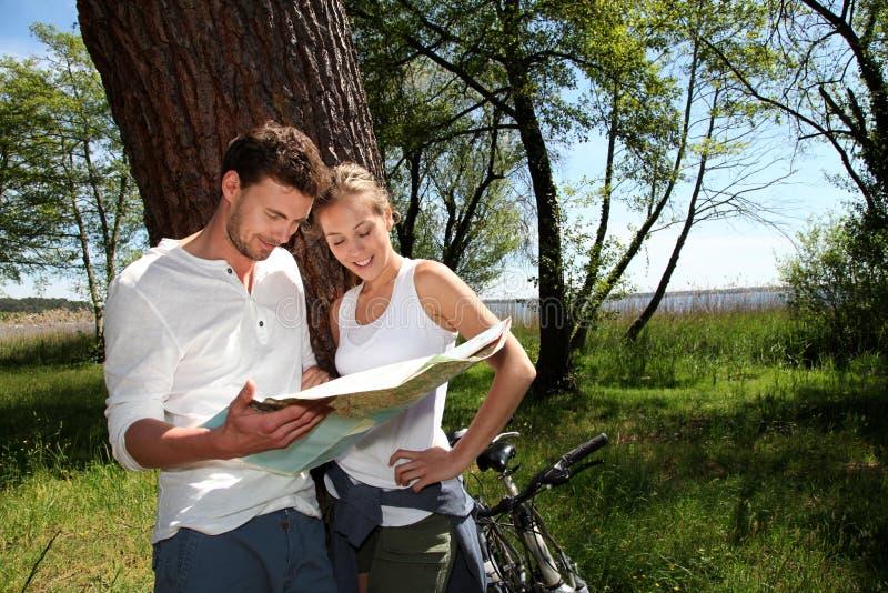 Jong paar op een fietsrit die kaart controleren stock foto's