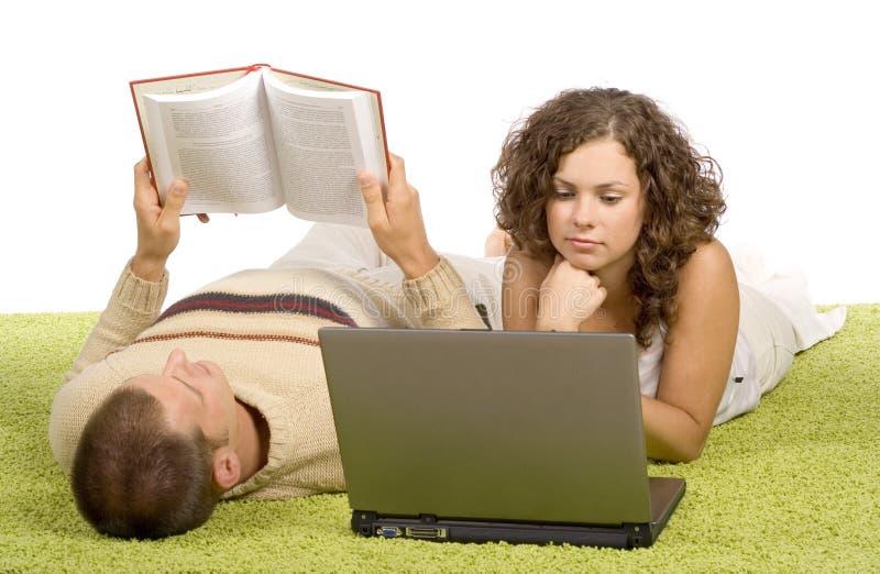 Jong paar op groen tapijt met laptop en boek royalty-vrije stock foto's