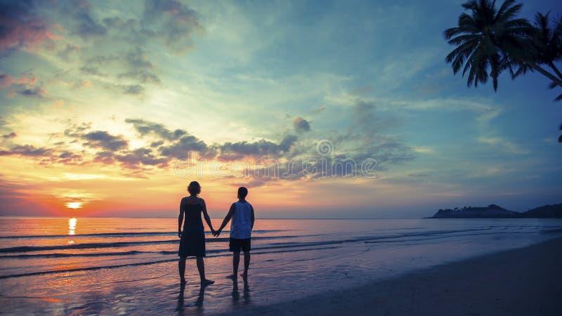 Jong paar op hun wittebroodsweken die zich op Overzees strand bij verbazende zonsondergang bevinden