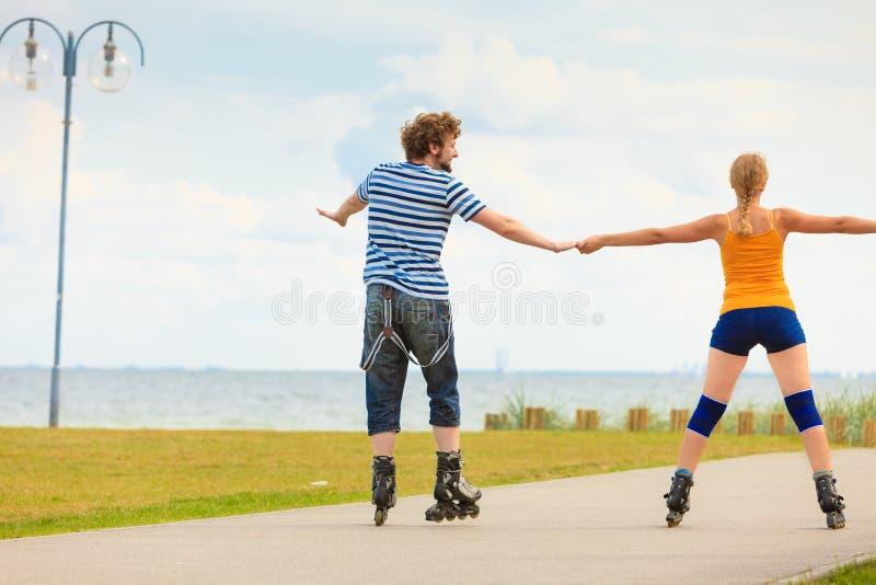 Jong paar op rolschaatsen die in openlucht berijden stock afbeeldingen