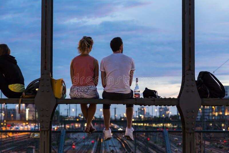 Jong paar op romantische datum op stedelijke spoorwegbrug, München, Duitsland stock foto's