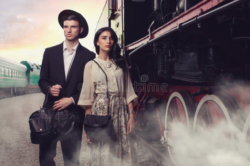 Jong paar op uitstekende spoorwegpost stock afbeeldingen