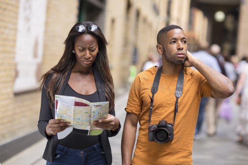 Jong paar op vakantie met een kaart royalty-vrije stock foto