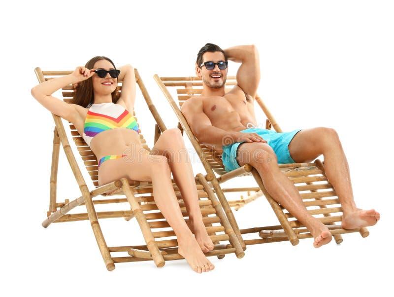 Jong paar op zonlanterfanters tegen wit De toebehoren van het strand stock foto
