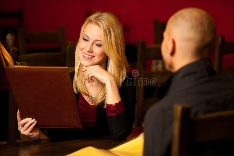 Jong paar ordeting voedsel in het menu van de restaurantlezing stock afbeelding