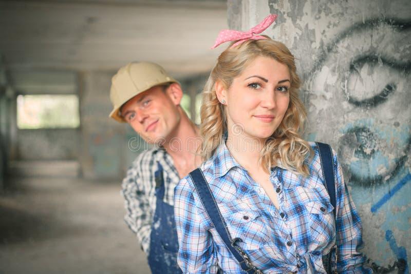 Jong paar in overall en helmen royalty-vrije stock afbeelding