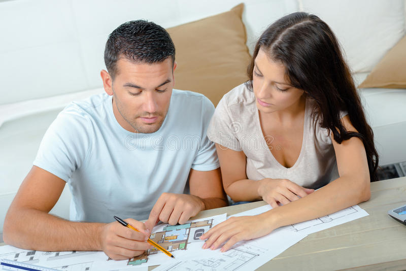 Jong paar planningsproject hun nieuw huis met blauwdruk royalty-vrije stock afbeelding