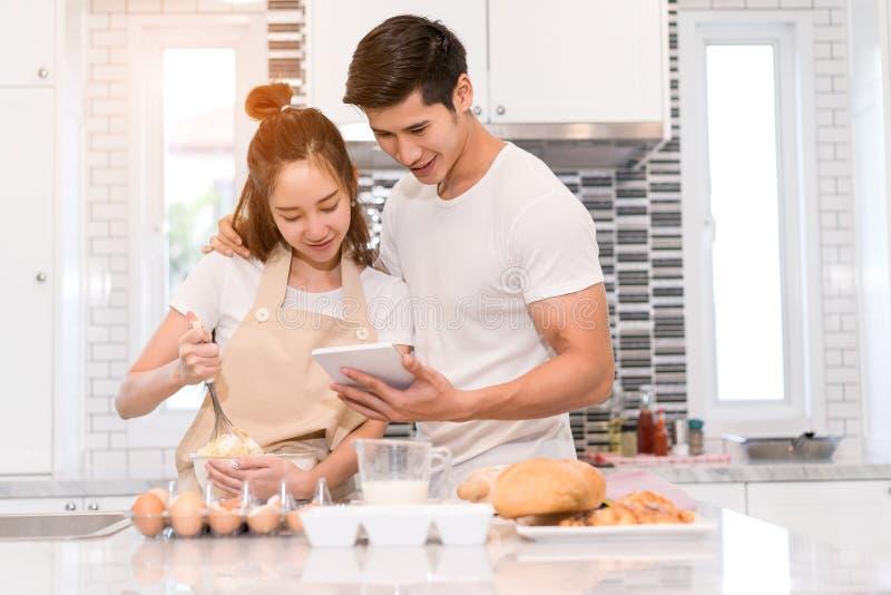 Jong paar samen het koken, Vrouwen eerste barst een ei en gezet in een kom royalty-vrije stock afbeeldingen